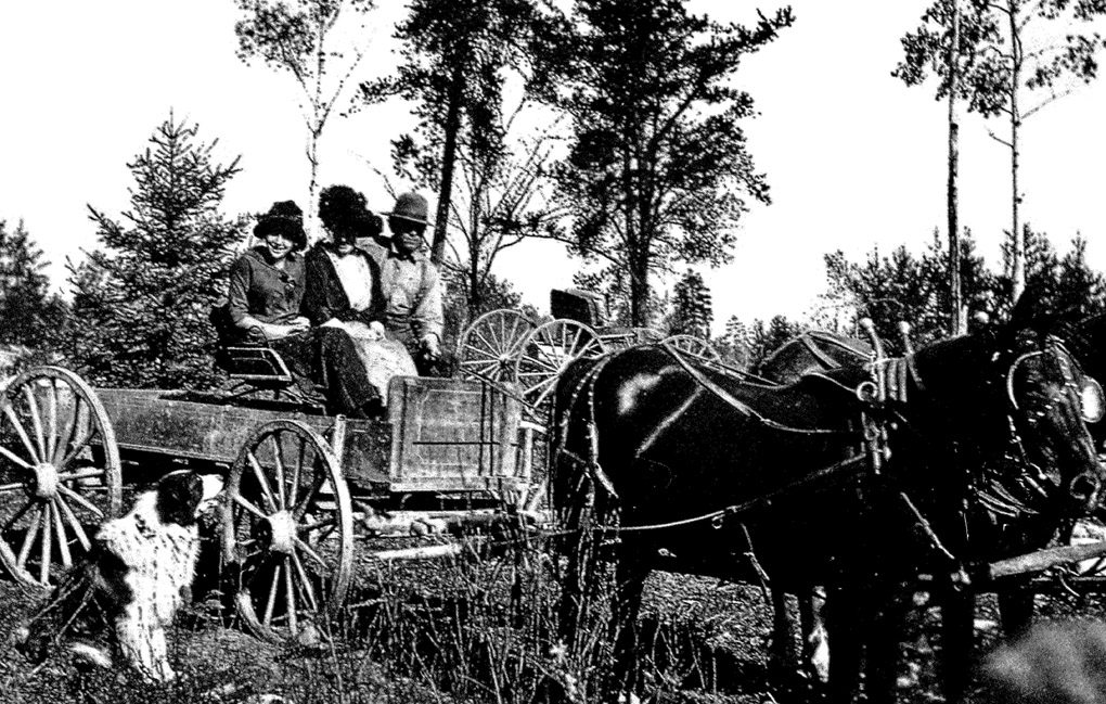 Image of early settlers in a wooden horse drawn wagon